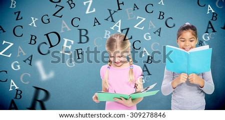 Elementary pupils reading against blue background - stock photo