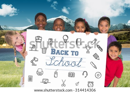 Elementary pupils showing card against scenic backdrop - stock photo