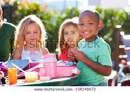 Elementary Pupils Sitting At Table Eating Lunch