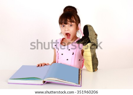 Elementary school aged girl being surprised at a book.  Also holding a snake puppet. - stock photo