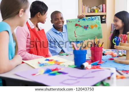 Elementary school art class with pupil discussing picture - stock photo