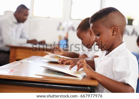 Elementary school boy reading a book in class, side view