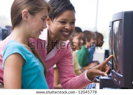 Elementary school computer class with teacher - stock photo