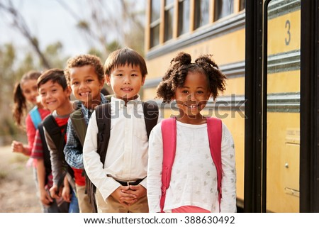 Elementary school kids queueing to get on to a school bus - stock photo