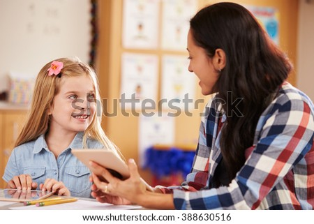 Elementary school pupil and teacher using tablet computer - stock photo