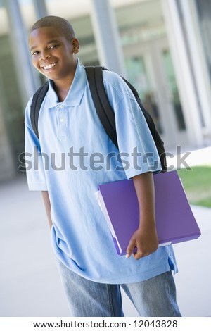 Elementary school pupil outside carrying folder - stock photo