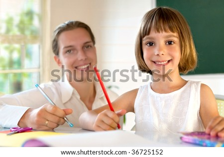 Elementary school pupil working with educator - stock photo