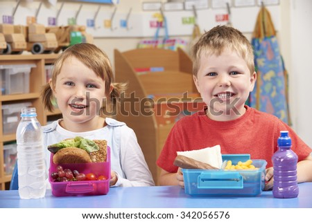 Elementary School Pupils With Healthy And Unhealthy Lunch Boxes - stock photo