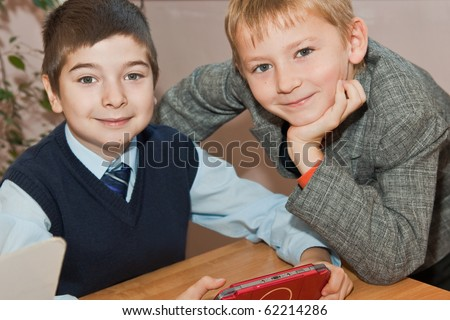 Elementary school. Schoolboys with  electronic game in the school - stock photo
