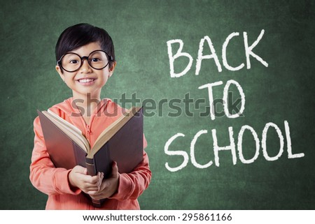 Elementary school student back to school and smiling on the camera while holding a textbook in the class - stock photo