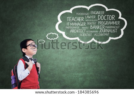 Elementary school student looking at his ideals on blackboard - stock photo