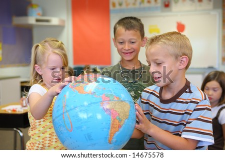 Elementary school students look at globe