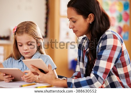 Elementary school teacher and pupil using tablet computers - stock photo