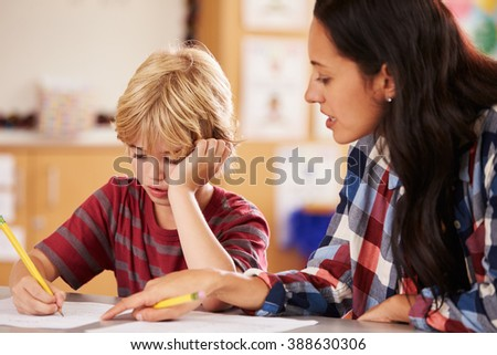 Elementary school teacher in class at desk with schoolboy