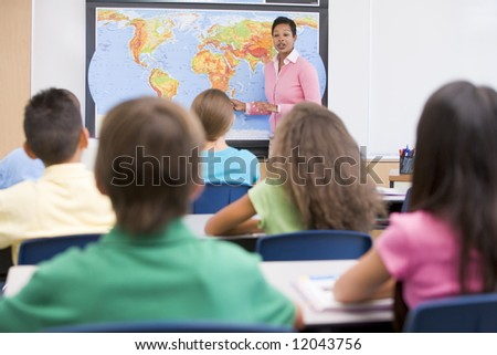 Elementary school teacher with pupils in geography class - stock photo
