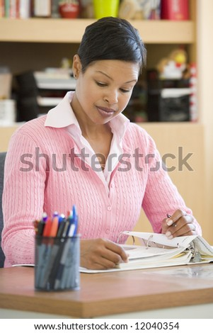 Elementary school teacher writing reports - stock photo