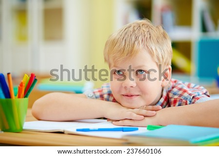Elementary schoolboy listening to his teacher at lesson - stock photo