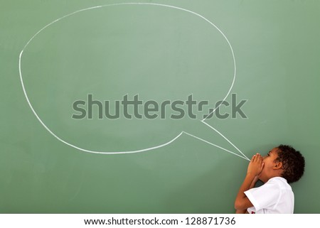 elementary schoolboy shouting at chat box drawn on chalkboard - stock photo