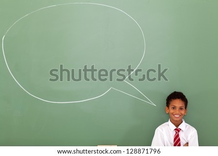 elementary schoolboy with speech bubble drawn on chalkboard - stock photo