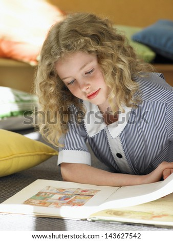 Elementary schoolgirl reading book on floor in classroom - stock photo