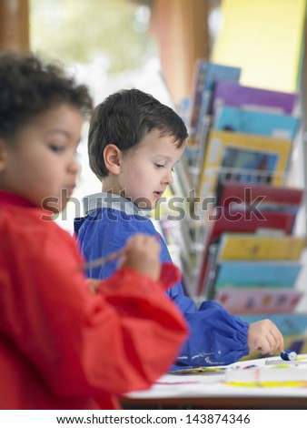 Elementary students painting in art class - stock photo