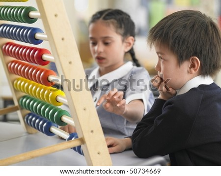 Elementary students using abacus in classroom - stock photo