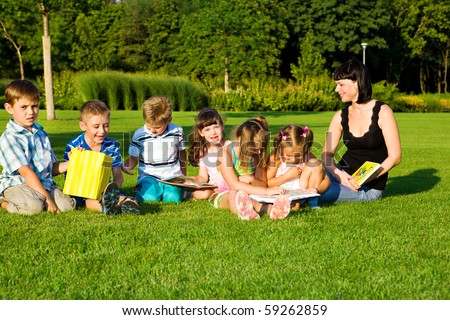 Elementary students with teacher in park - stock photo