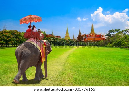 Elephant and tourists on an ride tour at the Buddhist temple of Wat Phra Kaeo at the Grand Palace in Bangkok,Thailand