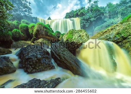Elephant Falls on a summer afternoon with old plaster stone structure, water, splashing, yellow water contains silt due from basaltic soils here are considered beautiful natural waterfall of Lam dong