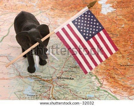 Elephant holding a US flag standing on a map of Iraq. - stock photo