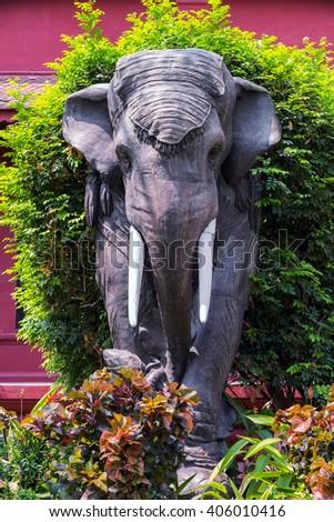 elephant statue with green shrub - stock photo
