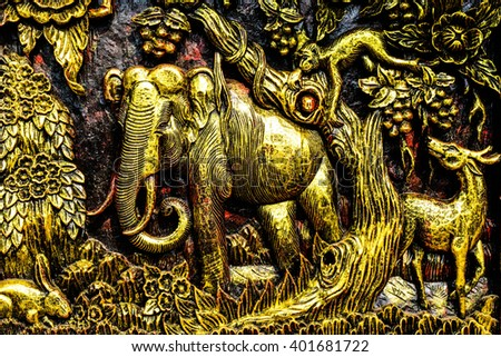 Elephant Thai wood carving on the temple wall. - stock photo