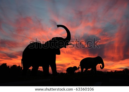 Elephants Enjoy a Spectacular Sunset on the Serengeti - stock photo