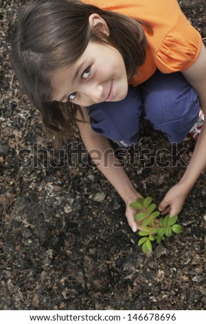 Elevated portrait view of a smiling girl planting black locust tree - stock photo