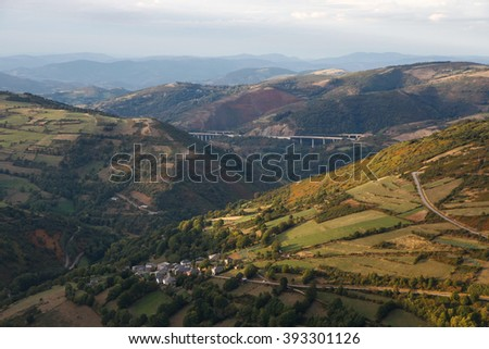 Elevated view from Pedrafita do Cebreiro,  of hilly landscape with villages, roads and viaducts in Galicia Spain. The people of Barxamaior in Los Ancares of Lugo and mountain horizon seen - stock photo