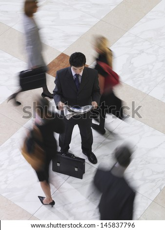 Elevated view of a businessman reading newspaper amongst blurred people walking on tiled floor