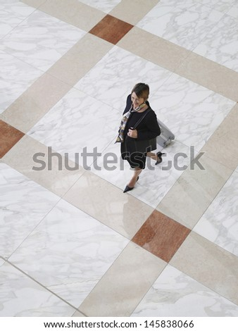 Elevated view of a businesswoman walking with suitcase on tiled floor - stock photo