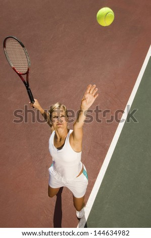 Elevated view of a female tennis player serving ball on court - stock photo