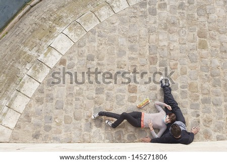 Elevated view of a loving couple relaxing on cobblestones