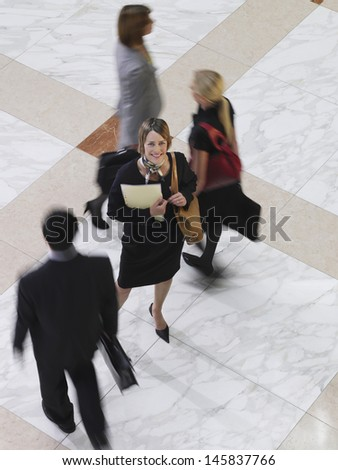 Elevated view of a smiling businesswoman amongst blurred people walking - stock photo