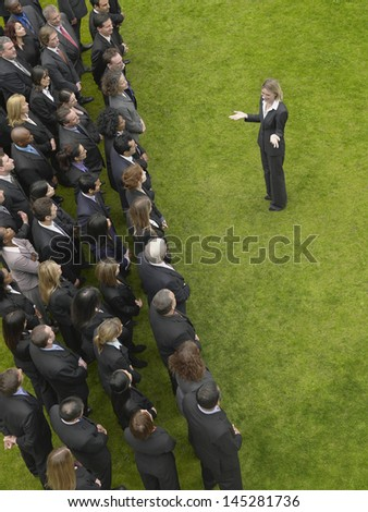 Elevated view of businesswoman facing large group of business people - stock photo
