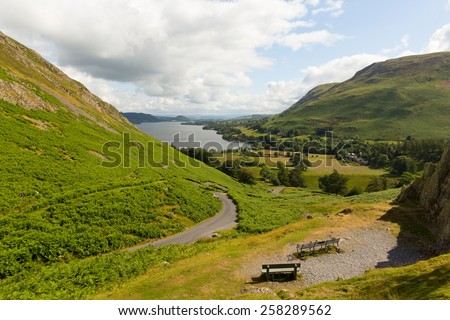 Elevated view of Ullswater Lake District Cumbria England UK from Hallin Fell with wooden bench seats in summer - stock photo