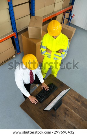 Elevated View Of Warehouse Worker And Manager Using Computer In A Warehouse - stock photo