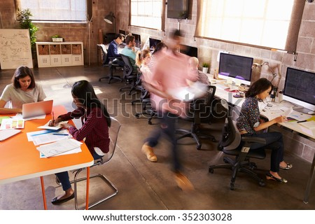 wide angle view busy design office. elevated view of workers in busy modern design office wide angle