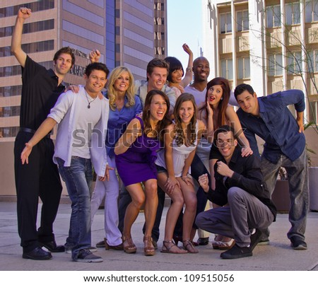 Eleven attractive young men and women enjoying each other at a party, smiling and celebrating on a balcony in the city