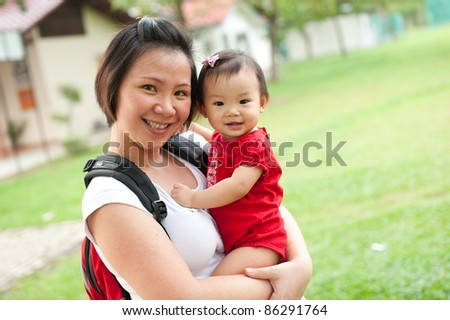 Eleven month old Asian baby girl and her mother in a park - stock photo