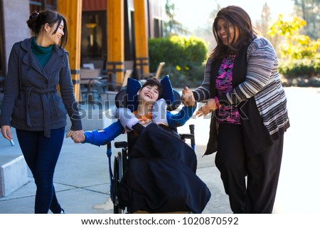 Eleven year old biracial disabled boy in wheelchair holding hands with caregivers while on a walk outdoors