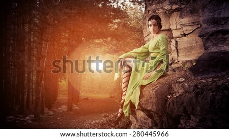Elf woman is sitting on the rocks. Forest on the background. - stock photo