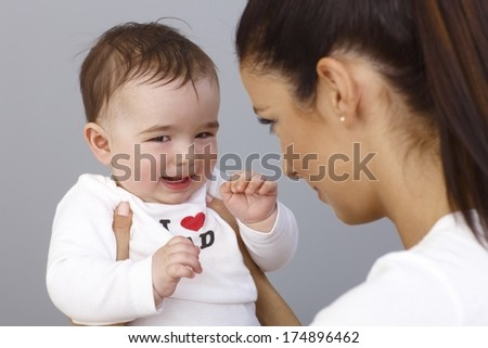 Elfish little boy smiling in mother's arms. - stock photo