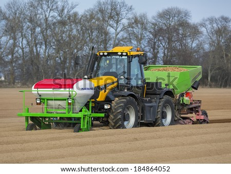 ELGIN, MORAY, SCOTLAND - 29 MARCH 2014: This is a tractor with all it's equipment planting potatoes within a field on the outskirts of Elgin, Moray, Scotland on 29 March 2014.